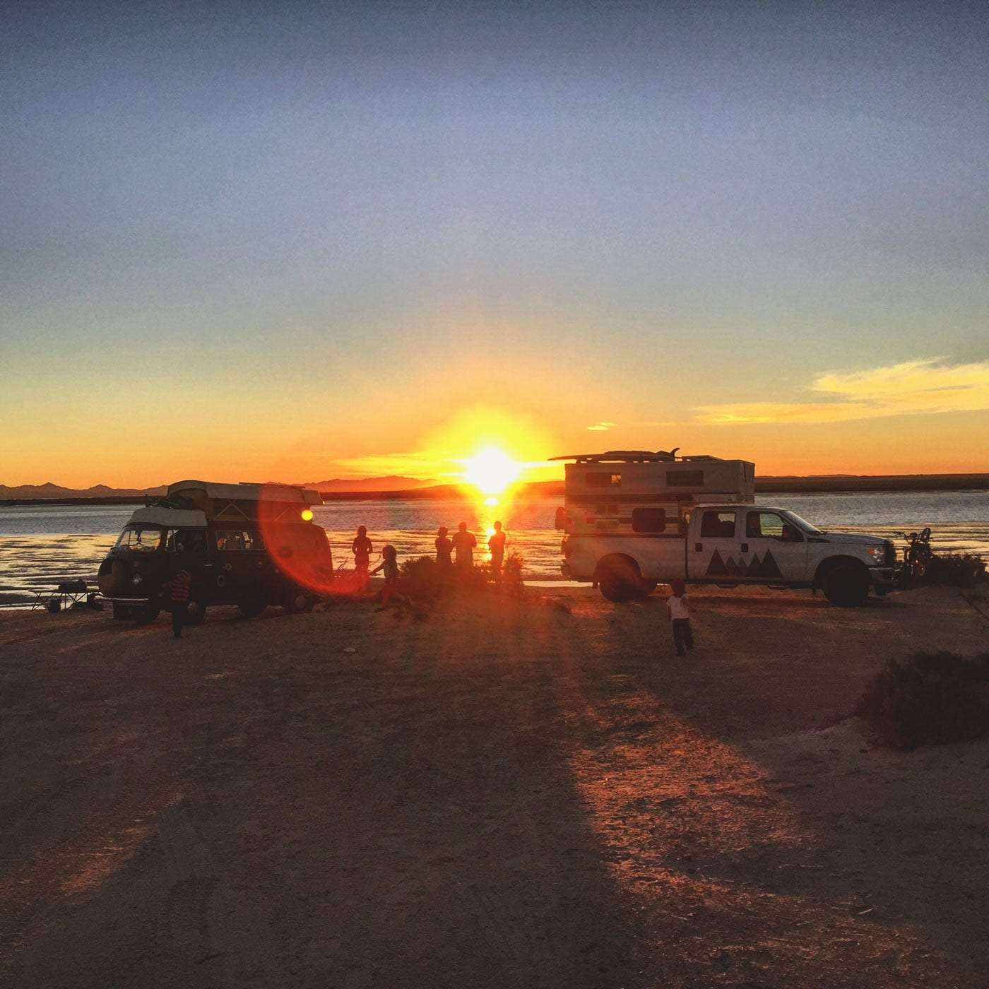 Sunset over the Pacific, a truck camper, volkswagen bus and their families surround
