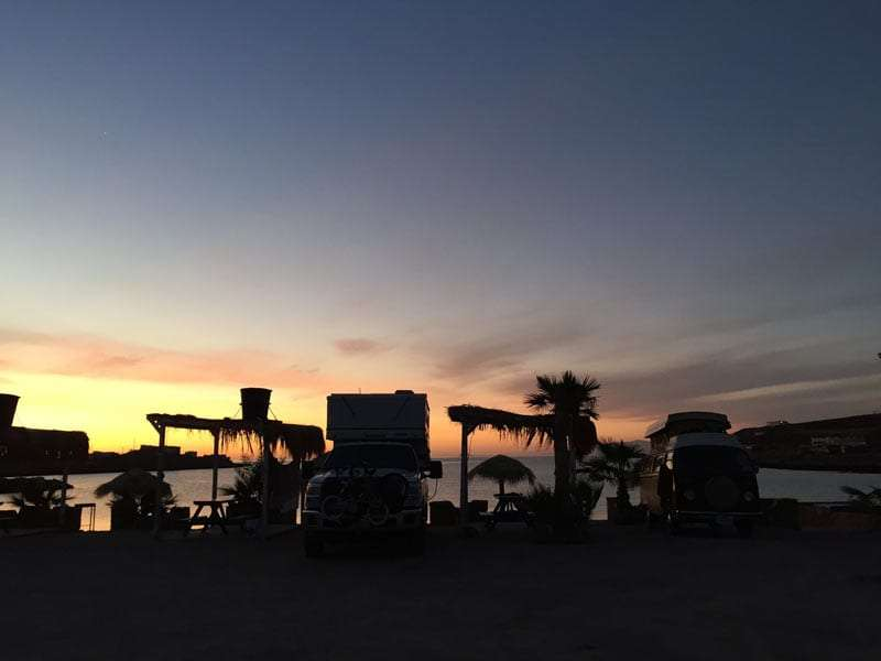 a campervan and a truck camper silhouetted against the Gulf of California in Puertocitos, Baja California.