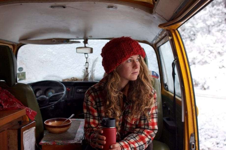 a young woman sitting in a volkswagen bus with a cup of tea and a bowl of food