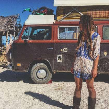 a beautiful woman stands in front of her beautiful VW bus
