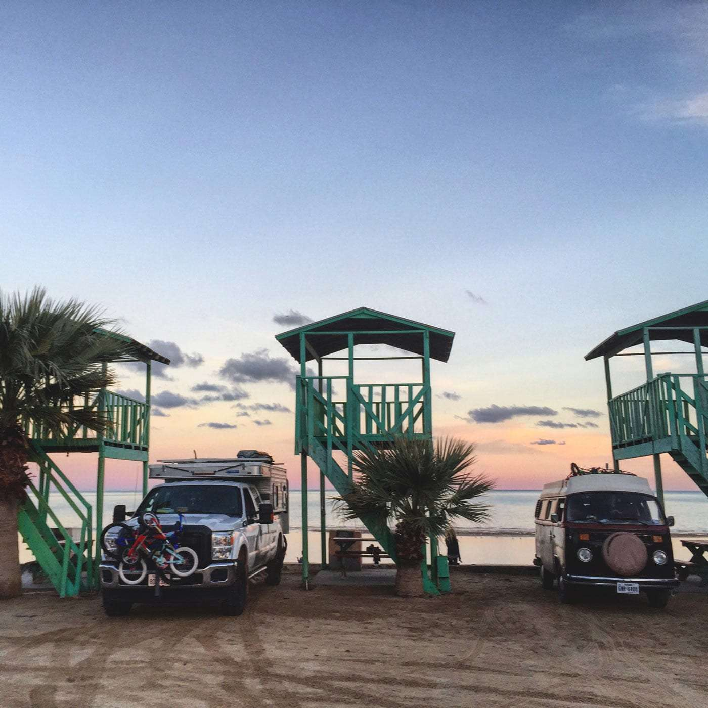 a Four Wheel Truck camper and a 1978 Volkswagen Bus parked beneath palapas in San Felipe