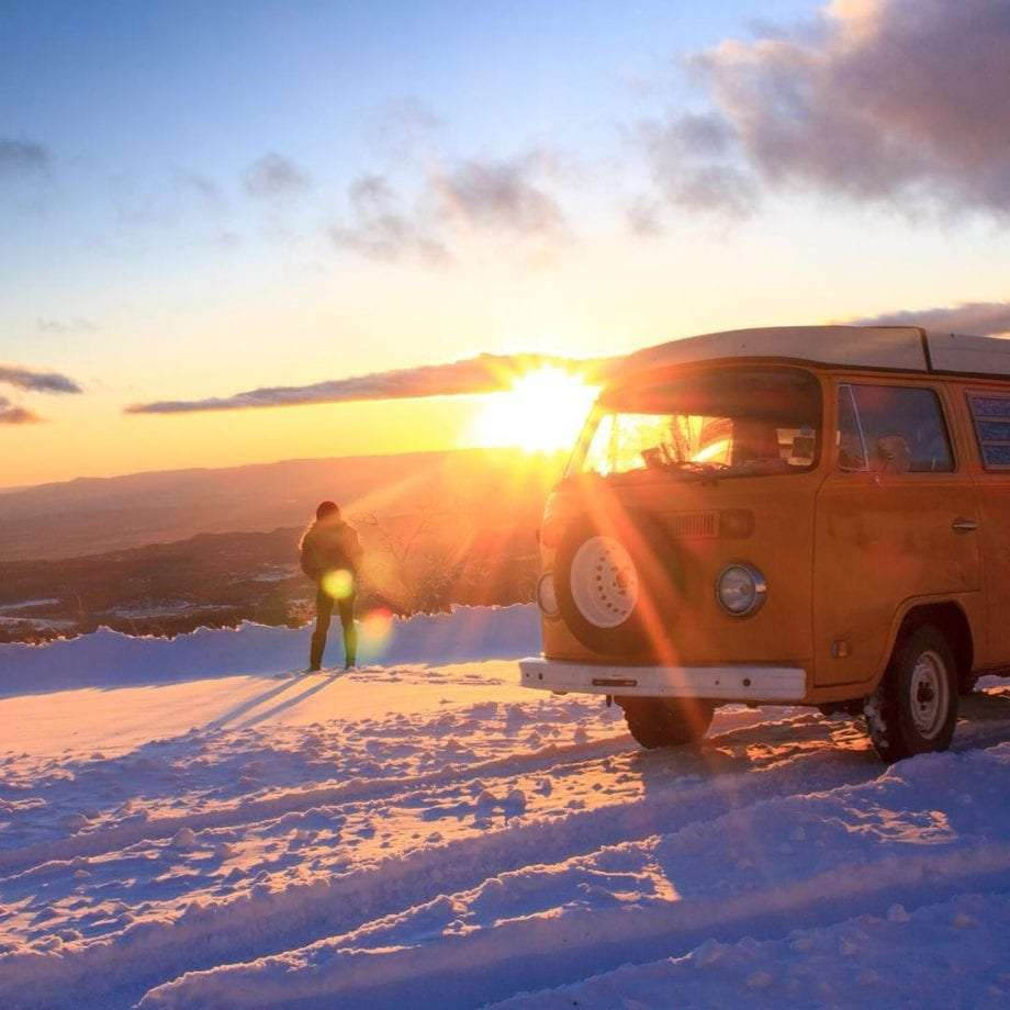 a woman and her VW Bus in the snow as the sun rises