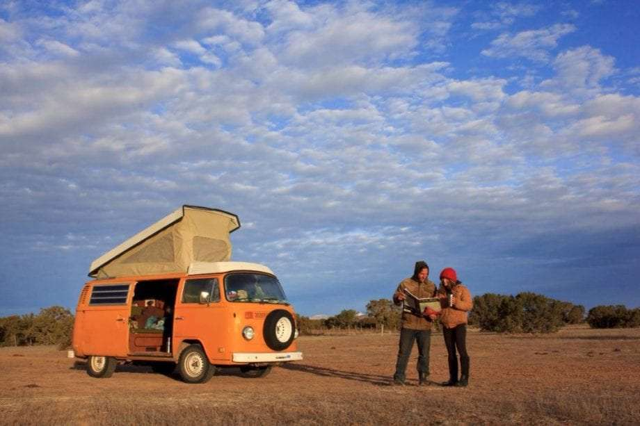 the young couple looking at their map, their westfalia campervan with its top popped