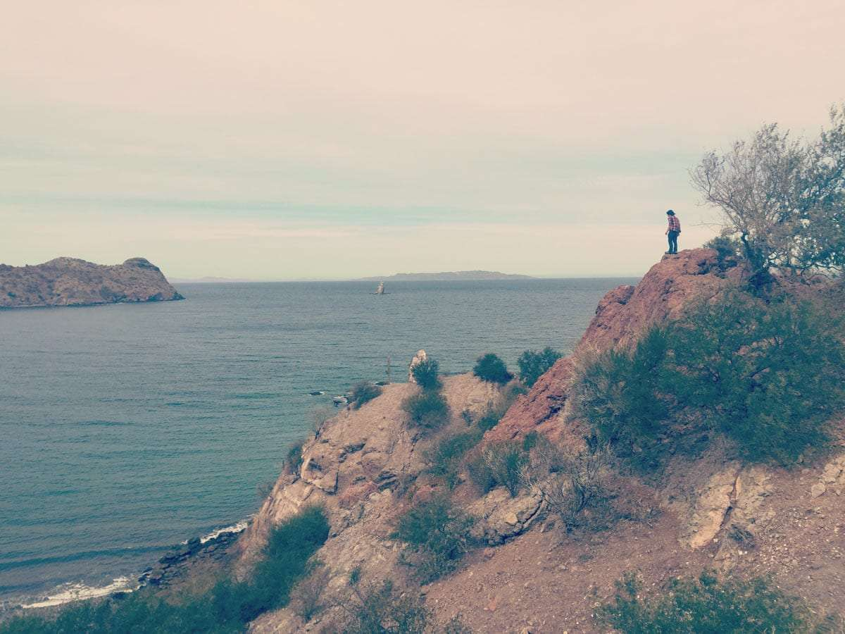 a teenage boy on a cliff overlooking the Gulf of California.