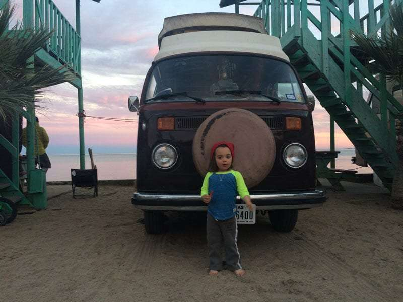 a toddler standing in front of a VW Bus