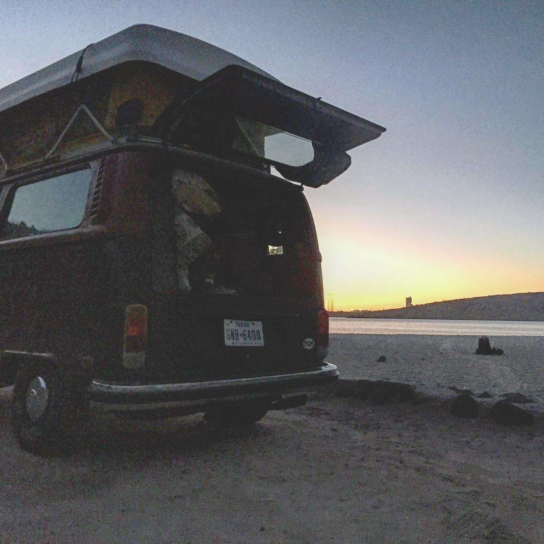 a Volkswagen Bus with the back door open, parked next to the sea of cortez at sunset