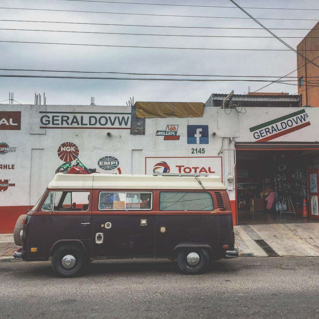 a 1978 champagne edition volkswagen bus parked in front of geraldo's in la paz, b.c.s., mexico