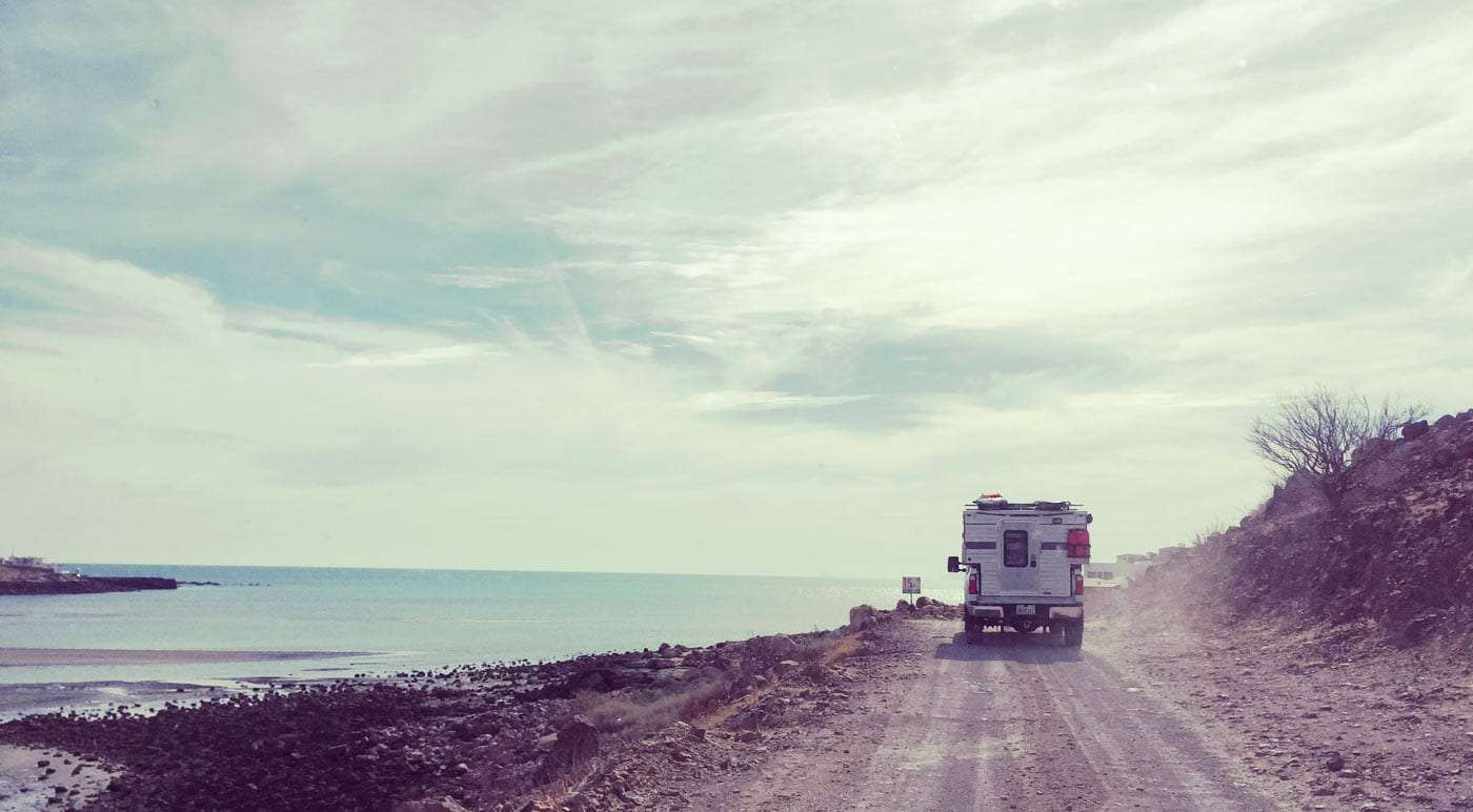 a Ford F-350 with a Four Wheel Drive truck camper (belonging to the Mali Mish family) drives down a dirt road in Mexico's Baja Peninsula