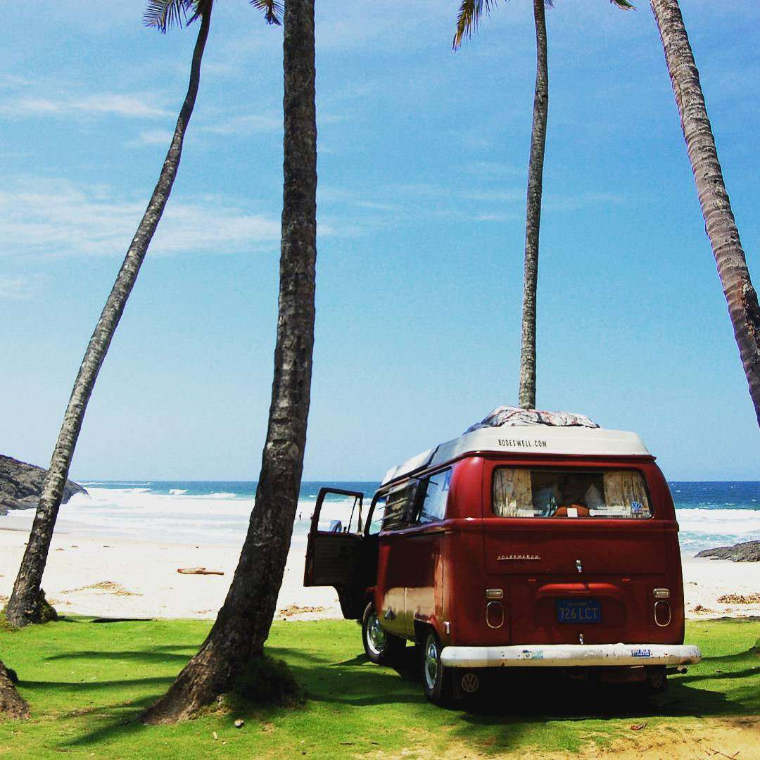 a Volkswagen Bus with the door open, parked near a beach