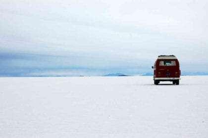 a red 1971 Volkswagen Bus parked on an endless desert beach