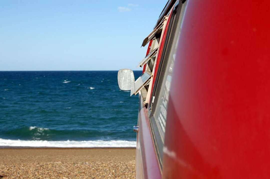 a shiny red paint job on a Volkswagen Bus parked on a beach somewhere, probably Mexico