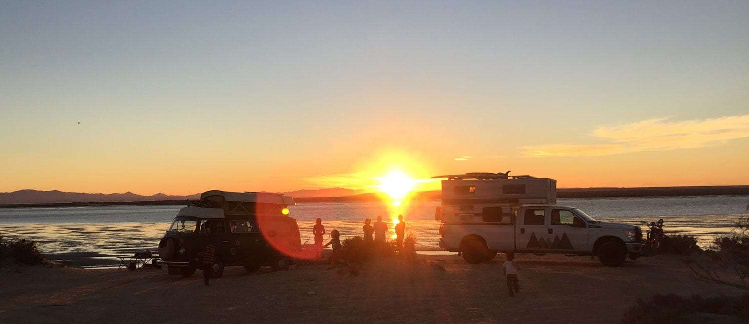 a VW Bus and a truck camper, two families totaling ten people, and a sunrise over Ojo de Liebre