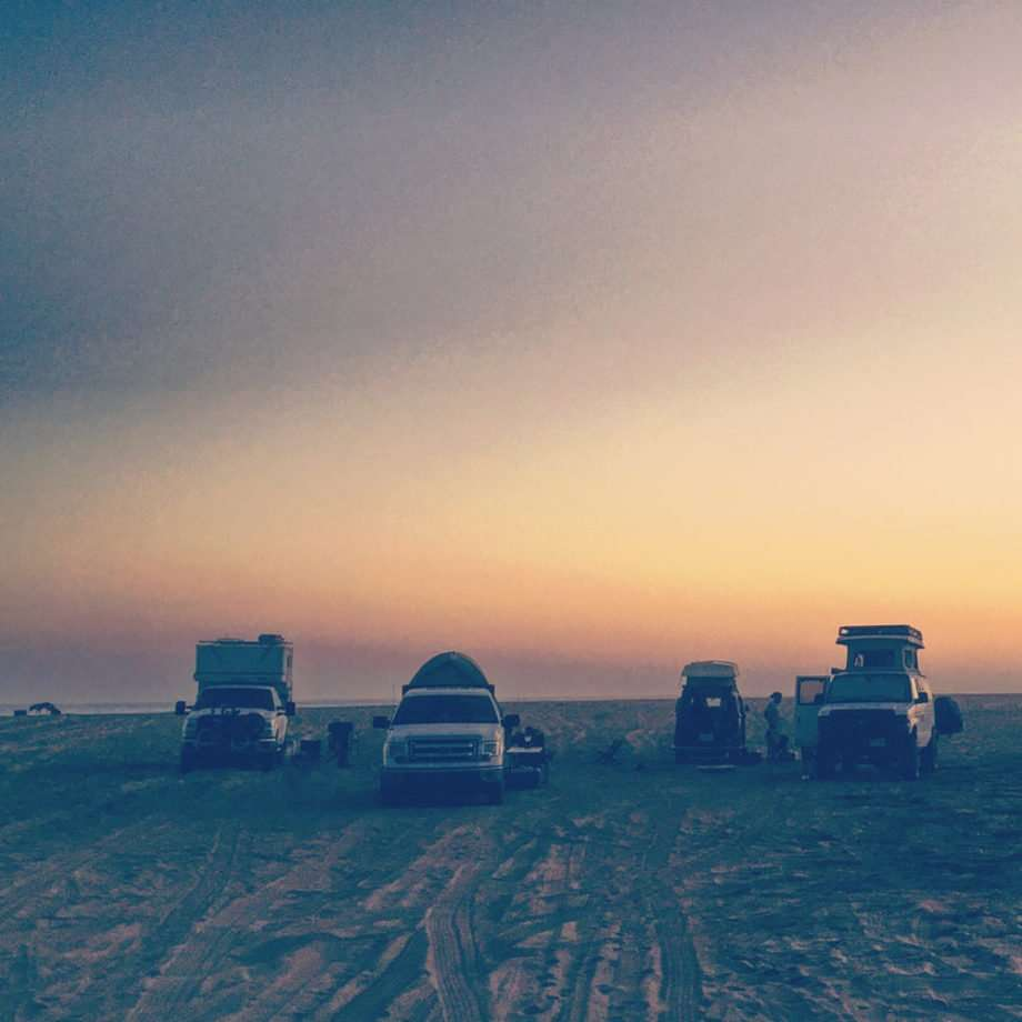 various types of overlanding vehicles camping on a beach at sunset