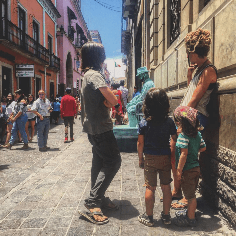 a family stands in Guanajuato near a street performer