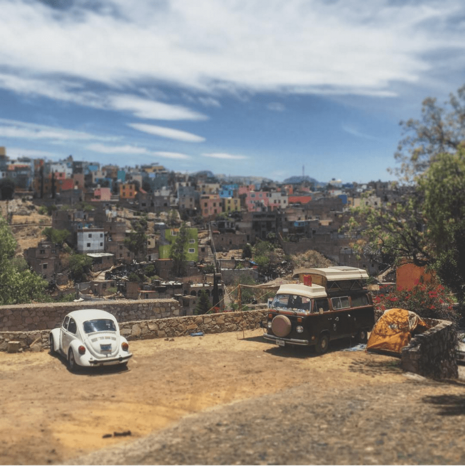 a Volkswagen Bus and Beetle parked against the Guanajuato backdrop