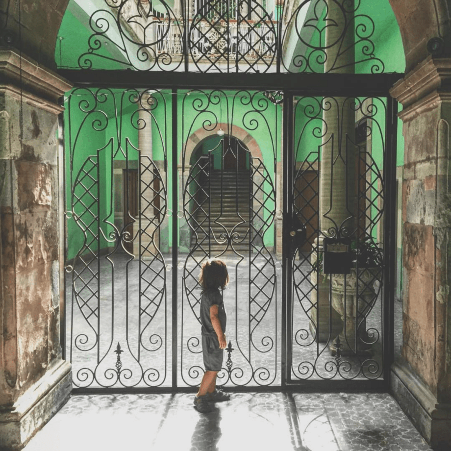 a young boy stands in front of a courtyard painted vivid green