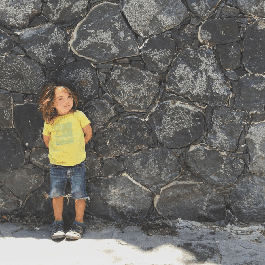 a young boy stands against a stone wall