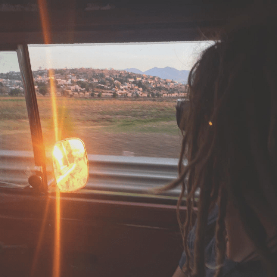 a beautiful woman with dreadlocks stares out of a window in a volkswagen bus, the mirror reflecting the sun