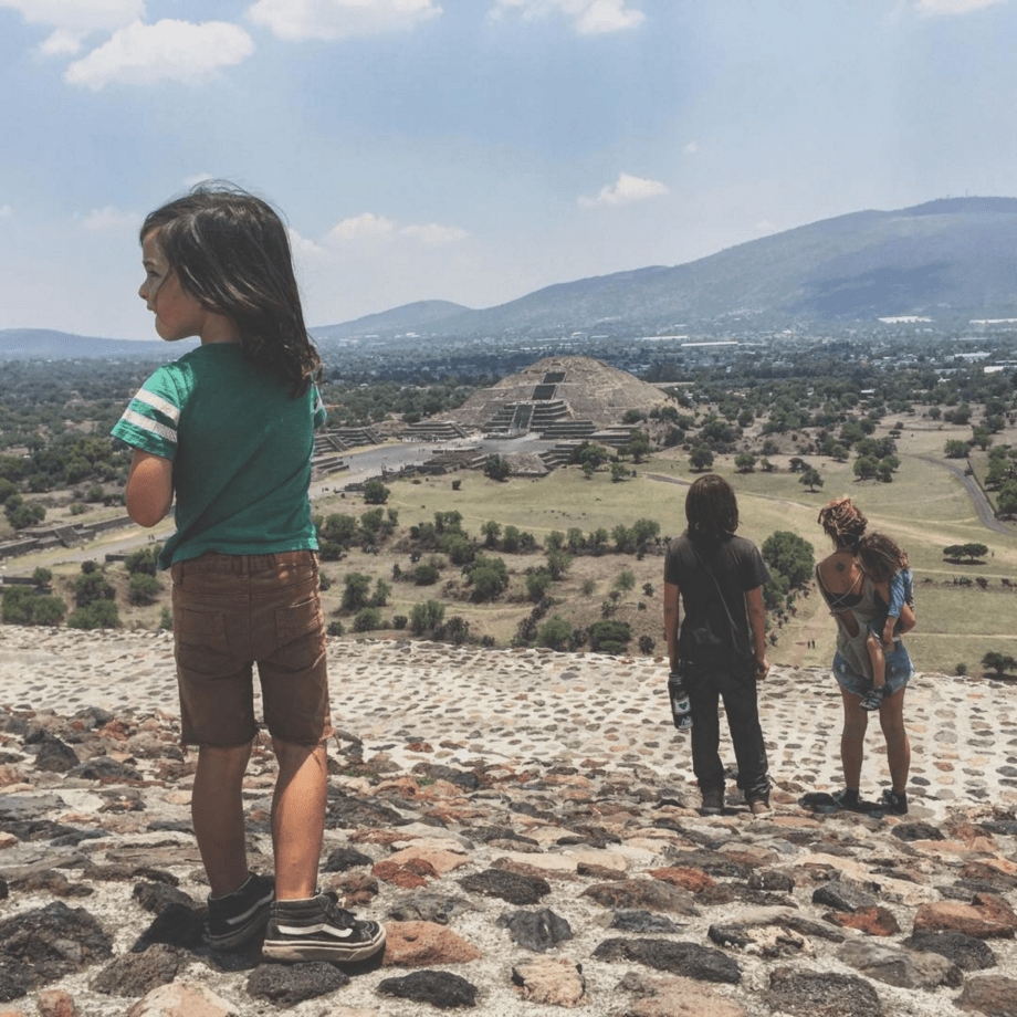 a young boy, his family in the distance, looks away from a pyramid