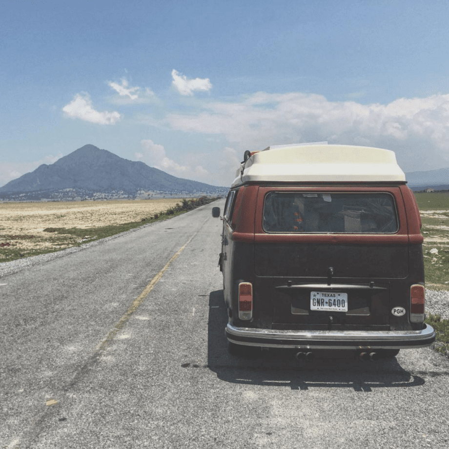 a triangular mountain, likely a volcano, rises behind a VW Bus parked on a lonely mexican road