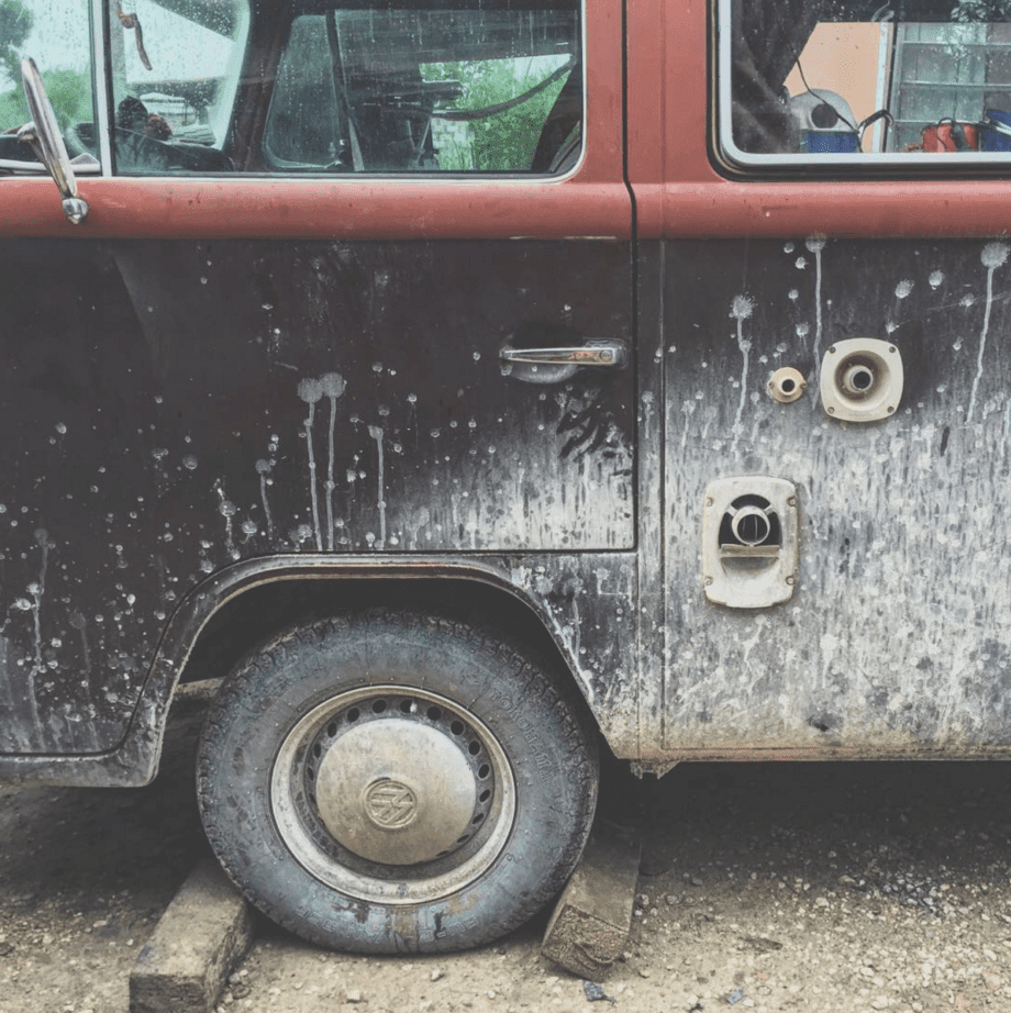 a dirty VW Bus with a flat tire and boards supporting it