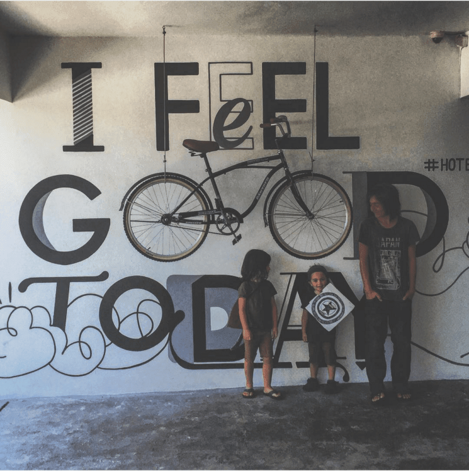 a wall in Chetumal Mexico reads I feel good today, three boys stand in front of it