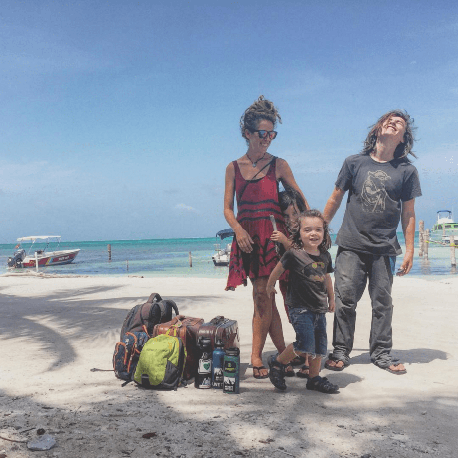 a young family laughs and loves on a beach just after arriving in belize