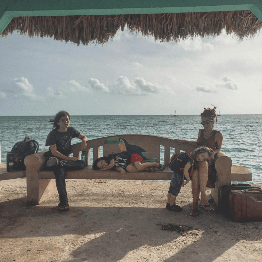 a family sits on a bench next to the Caribbean sea waiting for a water taxi