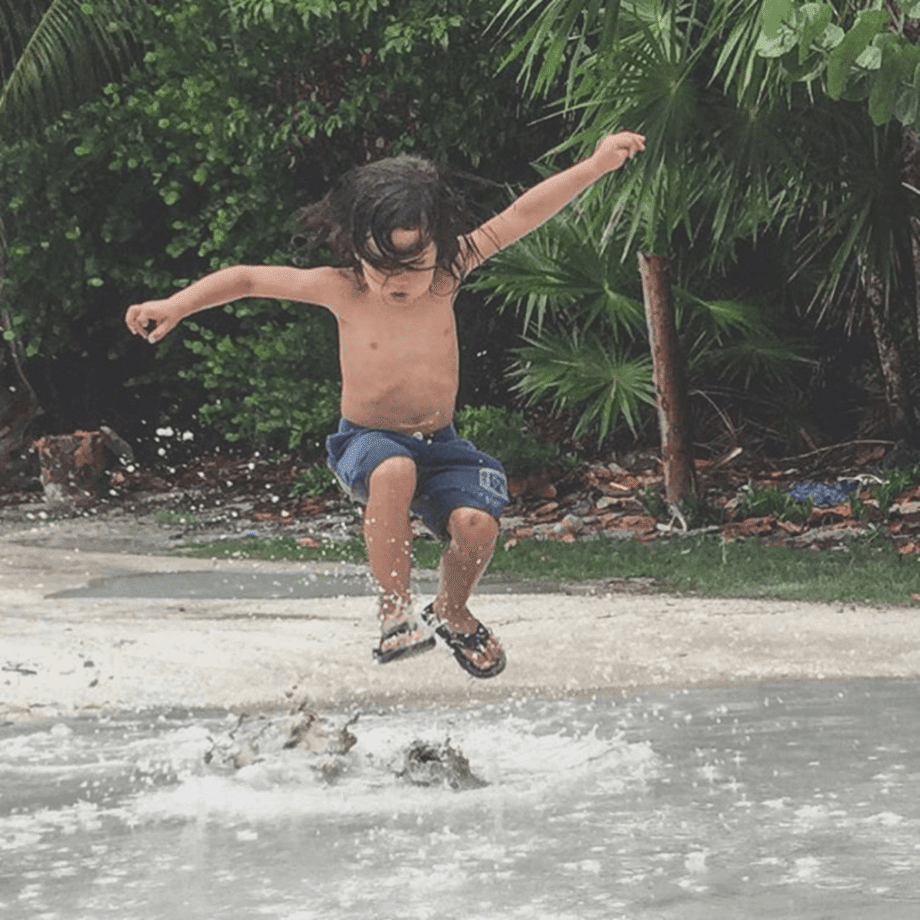 a young boy splashes in the water