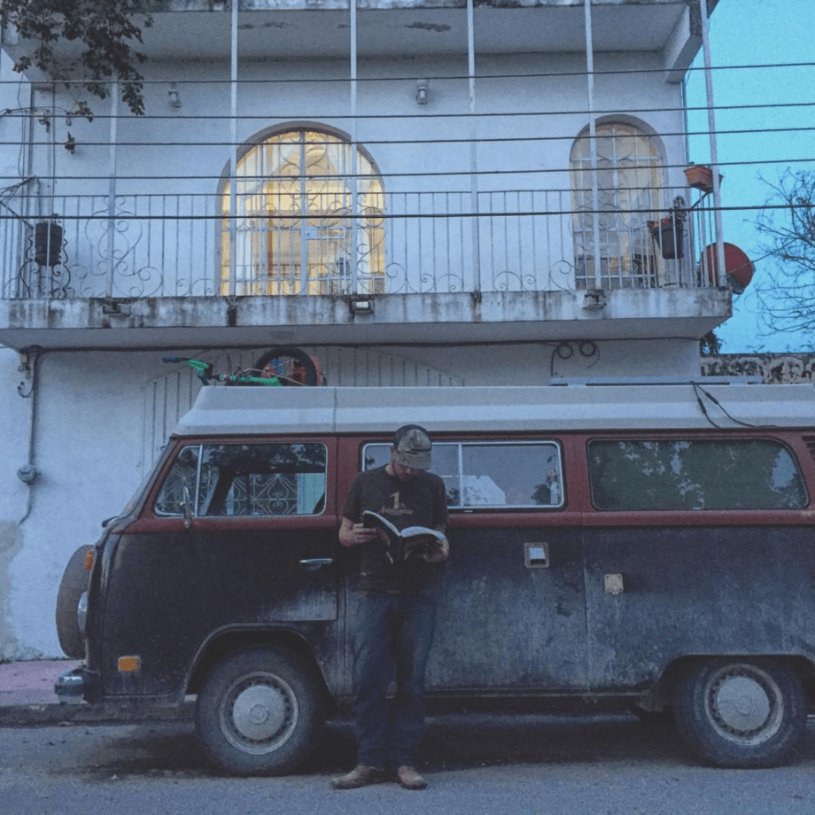 a man stands in front of his Volkswagen Bus, reading the compleat idiot guide to fixing air cooled vws