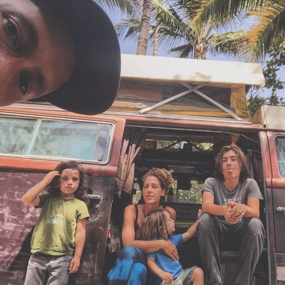 a family poses for a portrait in front of their 1978 volkswagen champagne edition bus