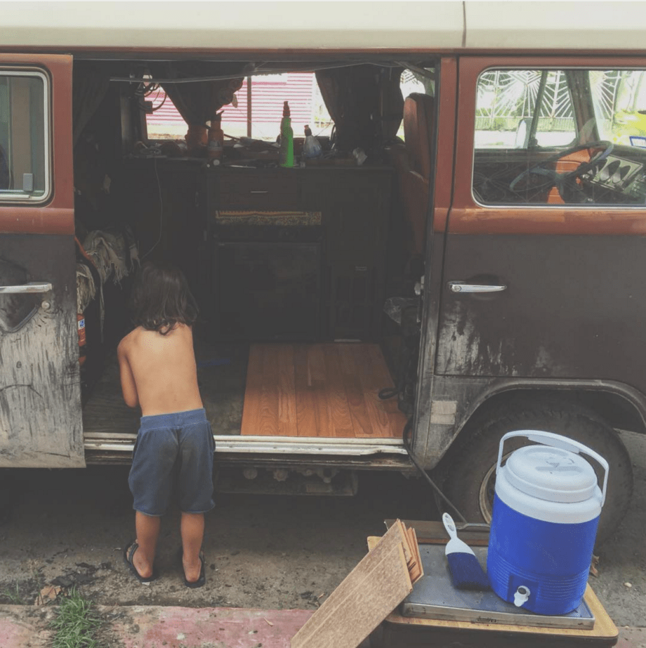 a young boy installing flooring into a vw bus