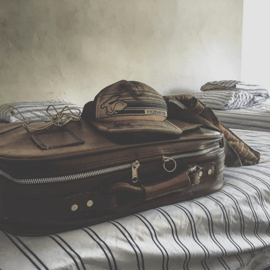 a dirty hat that reads Volkswagen and depicts a rabbit running quickly sits atop a beat up old suitcase with a laptop leaning against it