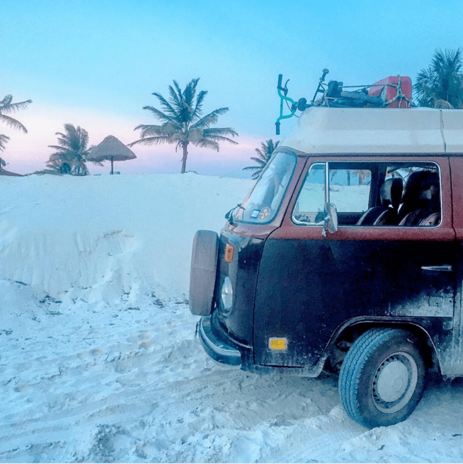 A VW Bus parked in the white sands near Tulum, MX
