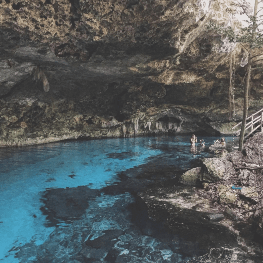 a pristine cenote, a family swims within