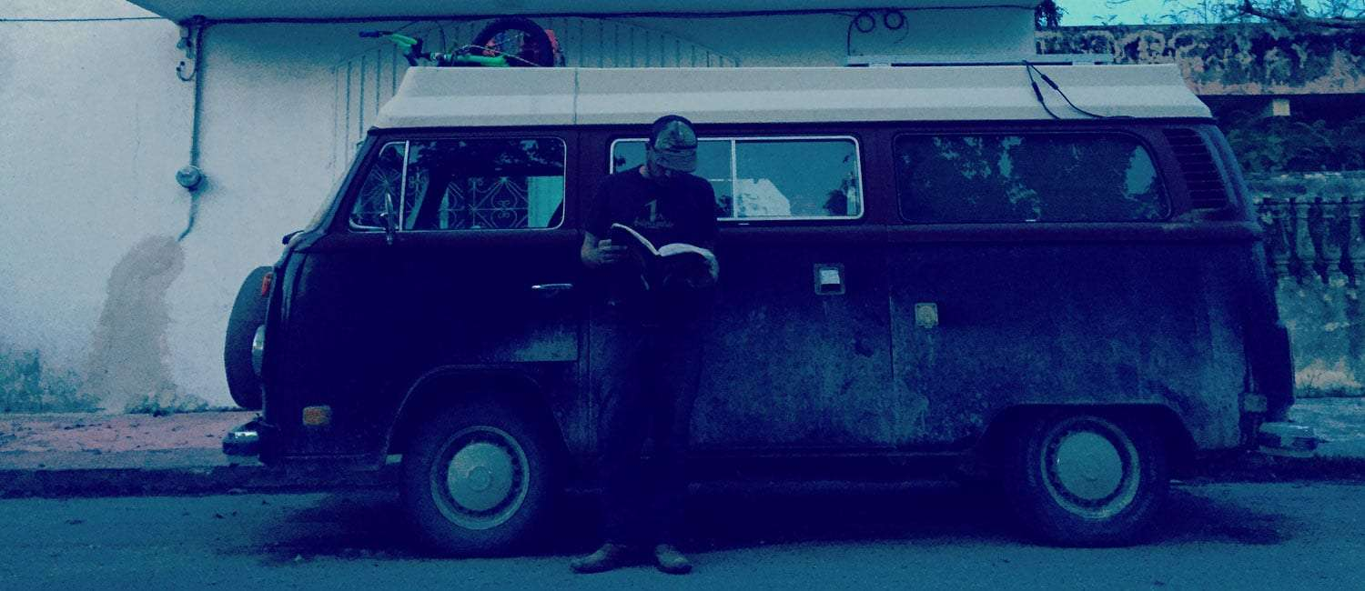 some guy standing in front of his 1978 volkswagen champagne edition bus reading a book about how to fix it