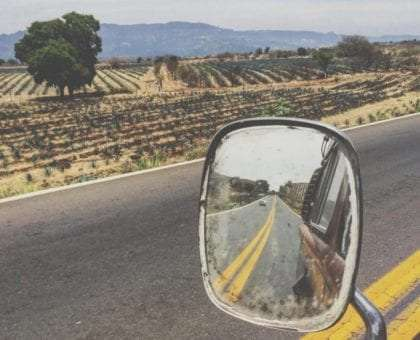 a mexican country road in the rear view of a vw bus driver mirror