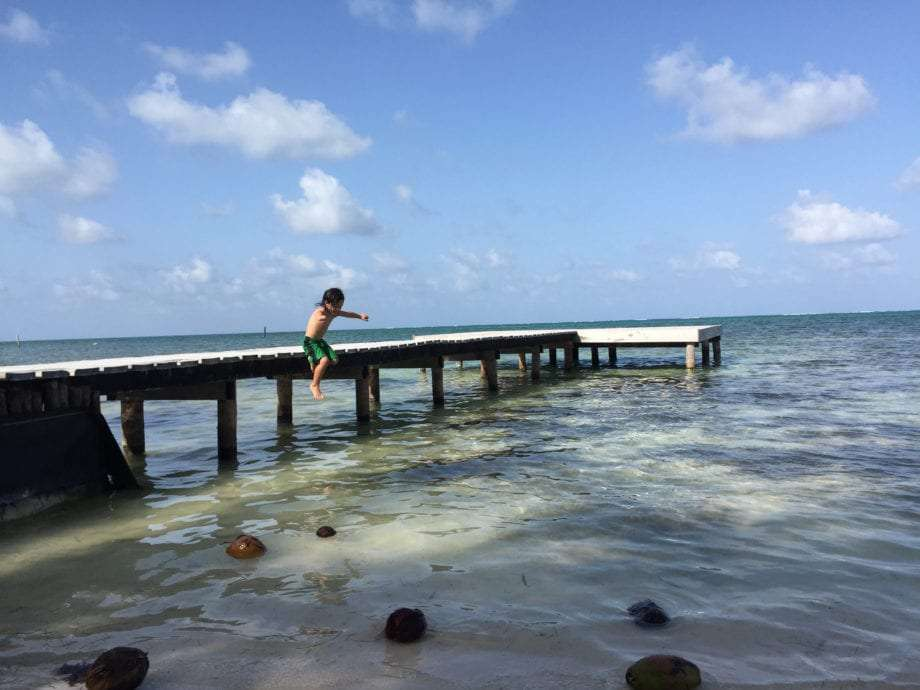 a young boy jumps from a dock into the caribbean sea