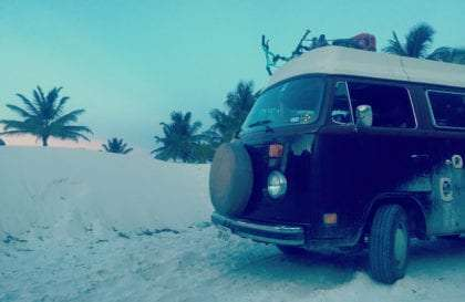 an old van parked on a beach, yay