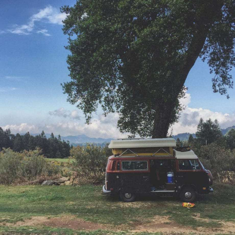 a volkswagen bus parked beneath a tree in mexico, atop mountains