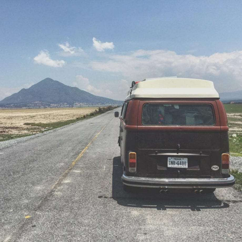 a 1978 champagne edition volkswagen Bus on the road in mexico