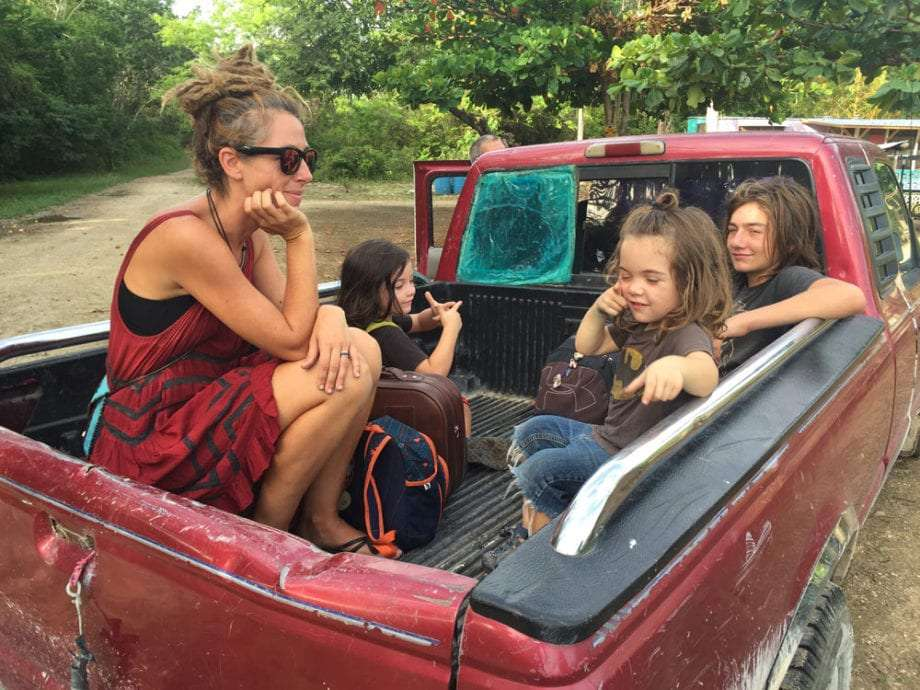 a family in the back of a pickup truck which swears it's a taxi