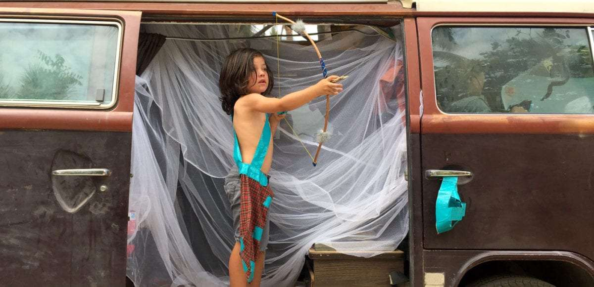 a young boy shoots a bow and arrow from a VW Bus in Mexico