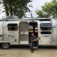 a dad works on his Macbook from the doorway of a vintage 1976 Airstream travel trailer