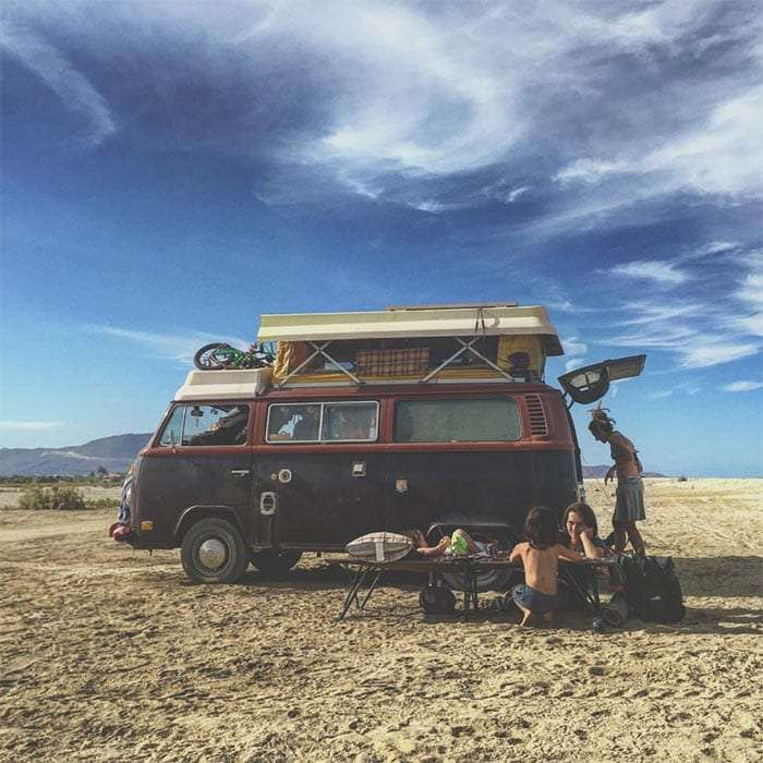a family doing school outside of their VW Bus on the beach
