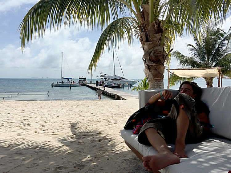 a teenager reads on a couch near the beach in isla mujeres, quintana roo, mexico