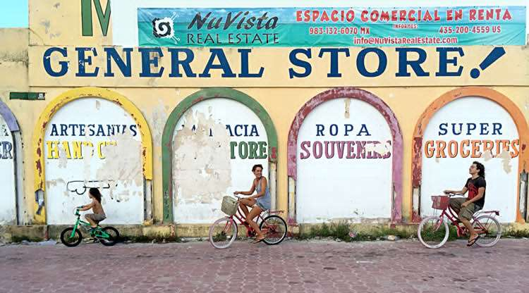 a family on bikes rides in front of a general store in Mahahual, Quintana Roo, Mexico