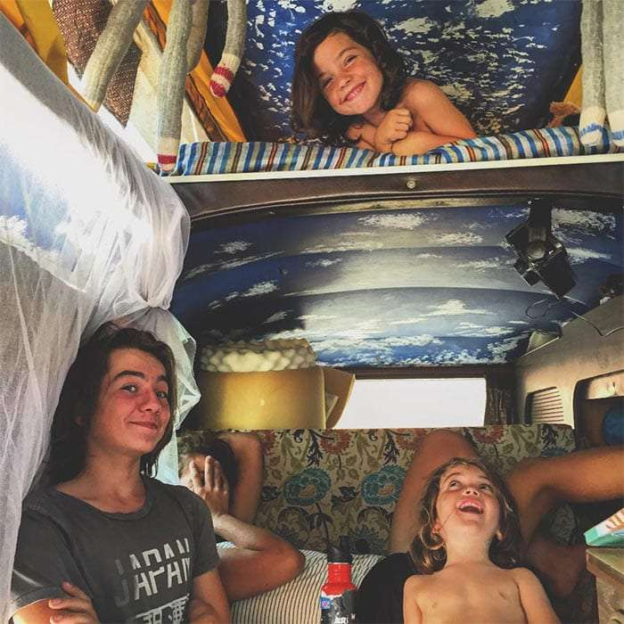 three boys laughing inside of a Volkswagen Bus, their mom covering her face in the background