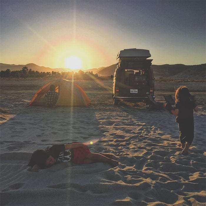 two boys play in the sand near a campervan and a tent, at sunset