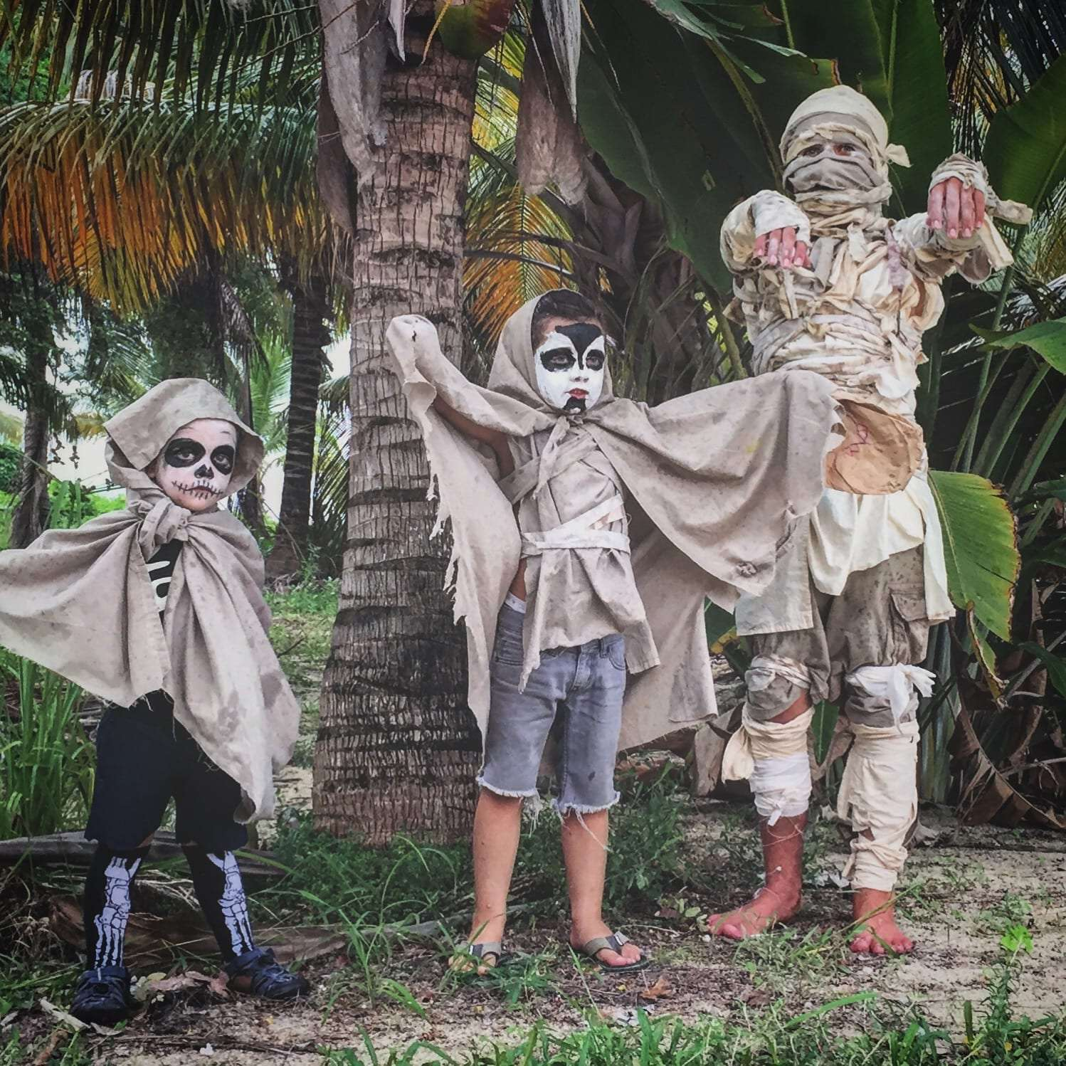 three children dressed up as mummies, skeletons and ghouls for Halloween in Belize